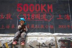 Enfant dans l'avant outre du roadsign, Thibet Photos stock