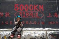 Enfant dans l'avant outre du roadsign, Thibet Image libre de droits