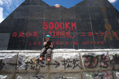 Enfant dans l'avant outre du roadsign, Thibet Images libres de droits