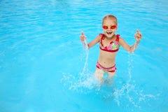 Enfant dans l'eau bleue de la piscine Photos stock
