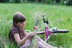 Enfant dans l'herbe avec le vélo Photographie stock libre de droits