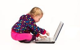 Enfant dans la dactylographie rose sur l'ordinateur portable, d'isolement images libres de droits