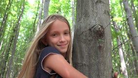 Enfant dans la forêt, enfant jouant en nature, fille dans l'aventure extérieure derrière un arbre clips vidéos