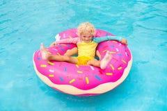 Enfant dans la piscine sur le flotteur de beignet photos stock