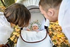 Enfant dans la poussette regardant aux parents photographie stock libre de droits