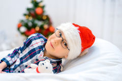 Enfant dans le chapeau de Santa se trouvant sur le sofa avec l'ours de nounours Image libre de droits