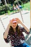 Enfant dans le chapeau rose balan?ant sur le terrain de jeu - forme de coeur photographie stock