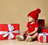 Enfant dans le chapeau rouge avec des piles de boîtes actuelles autour de se reposer sur le plancher photos libres de droits