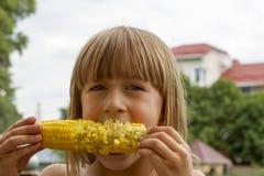 Enfant dans le jardin - belle fille mangeant l'épi de maïs photos libres de droits