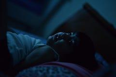 Enfant dans le lit la nuit Images stock