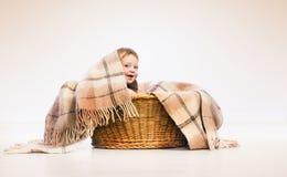Enfant dans le panier avec la serviette Textile et literie pour des enfants Images stock