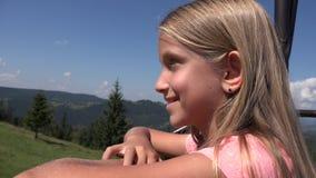 Enfant dans le télésiège, fille de touristes en Ski Cable, enfant en montagnes ferroviaires, alpines banque de vidéos