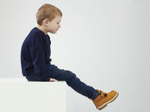 Enfant dans les bottes jaunes Enfants de mode Enfants petit garçon s'asseyant sur un cube Images libres de droits