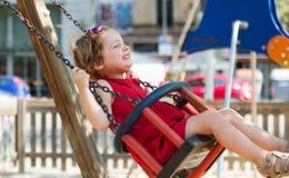 Enfant dans les dres rouges sur l'oscillation à chaînes Photographie stock libre de droits