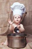Enfant dans un capot de cuisine photo stock