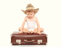 Enfant dans un chapeau d'été de paille se reposant sur la valise Photos stock