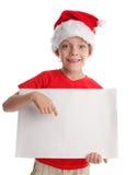 Enfant dans un chapeau de Noël et la forme dans des mains Photographie stock libre de droits