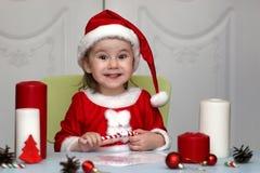 Enfant dans un costume de Santa Claus écrivant une lettre avec des souhaits pour Photos libres de droits