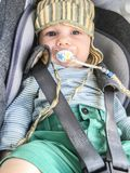 Enfant dans un siège de voiture avec le simulacre du bébé photo libre de droits