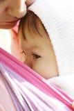 Enfant dans une élingue de chéri Photographie stock libre de droits