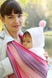 Enfant dans une élingue de chéri. Images stock