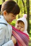 Enfant dans une élingue de chéri. Photos libres de droits