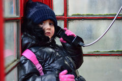 Enfant dans une cabine téléphonique rouge, au téléphone Photos libres de droits