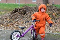 Enfant dans vêtements et capot chauds avec la bicyclette d'équilibre images libres de droits