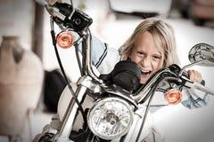 Enfant débarrassé des plants peu vigoureux conduisant une moto Photos libres de droits