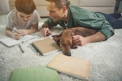 Enfant de aide d'homme joyeux pour faire des devoirs près de l'animal familier Photographie stock