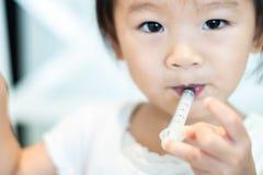 Enfant de bébé non effrayé de s'alimenter avec la médecine liquide avec la seringue image stock