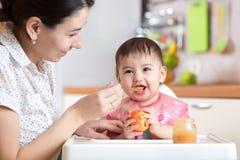 Enfant de bébé s'asseyant dans la chaise avec une cuillère et mangeant de la nourriture saine images stock
