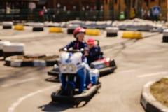 Enfant de Blured conduisant la voiture de kart avec la vitesse dans une voie d'emballage de terrain de jeu photos stock