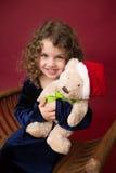 Enfant de Chirstmas avec le jouet : Fond rouge d'hiver de vacances Photographie stock libre de droits