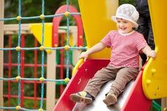 Enfant de deux ans heureux sur la glissière Photos stock