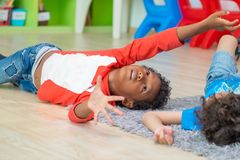 Enfant de deux garçons se situant sur le plancher et le jeu ensemble dans librar préscolaire Photos libres de droits