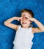 Enfant de dissimulation de garçon heureux sur le tapis bleu dans le salon à la maison photo stock
