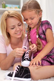Enfant de enseignement de mère comment attacher des chaussures Photos libres de droits