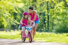 Enfant de enseignement de mère pour monter un vélo images libres de droits