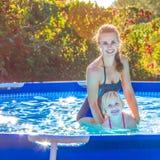 Enfant de enseignement de sourire de mère active à nager dans la piscine Photographie stock