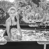 Enfant de enseignement de sourire de mère active à nager dans la piscine Images libres de droits