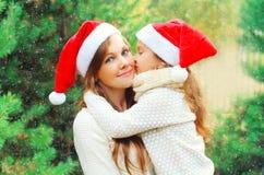 Enfant de famille de Noël embrassant la mère dans des chapeaux rouges de Santa ensemble au-dessus de l'arbre Photographie stock libre de droits