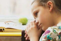 Enfant de fille à la fenêtre, livre sur un rebord de fenêtre Images libres de droits