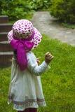 Enfant de fille dans la robe d'été et le chapeau rose pour une promenade, vue du dos images libres de droits