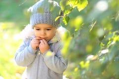 Enfant de fille dans le chapeau et le manteau jouant sur le fond naturel photo stock