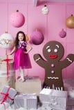 Enfant de fille de brune 5 années dans une robe rose dans la pièce de quartz rose de vacances avec des cadeaux images stock