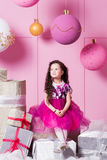 Enfant de fille de brune 5 années dans une robe rose dans la pièce de quartz rose de vacances avec des cadeaux images libres de droits