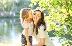 Enfant de fille embrassant la mère heureuse en été Photo libre de droits
