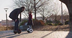 Enfant de fille embrassant son papa montant le hoverboard segway Future technologie moderne de transport Famille actif Trottoir d banque de vidéos