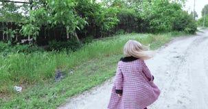 Enfant de fille marchant sur une rue rurale banque de vidéos